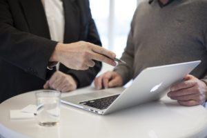 パソコン画面に二人向き合って話している写真|KEN'S BUSINESS(ケンズビジネス)|職場問題の解決サイト中間管理職・サラリーマン・上司と部下の「悩み」を解決する情報サイト