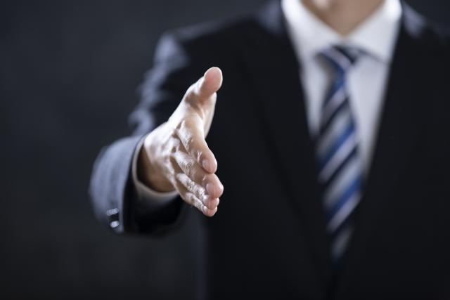 3.攻撃的な態度はとらない|握手しようとする男性の写真|社内で意見が合わない時の対処法