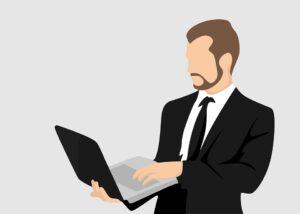 立ってパソコンを操作している男性の写真 KEN'S BUSINESS ケンズビジネス 職場問題の解決サイト中間管理職・サラリーマン・上司と部下の「悩み」を解決する情報サイト