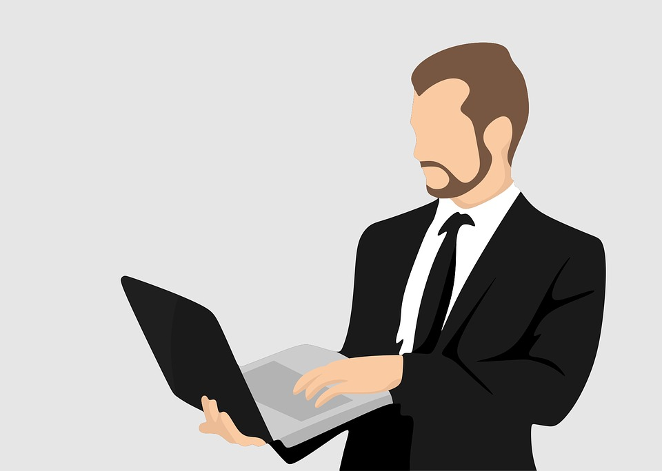 立ってパソコンを操作している男性の写真|KEN'S BUSINESS|ケンズビジネス|職場問題の解決サイト中間管理職・サラリーマン・上司と部下の「悩み」を解決する情報サイト